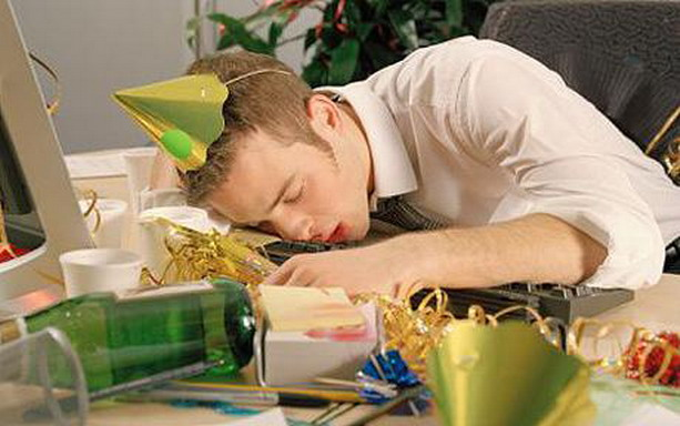 Young man asleep at desk, surrounded by remnants of office party